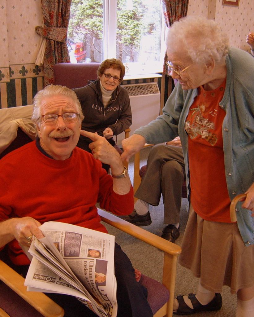 A group of care home residents doing a drama role play activity.