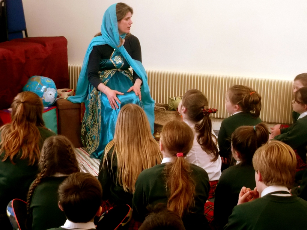A storyteller with school children at a library.